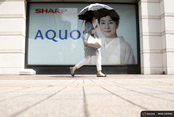 A woman holding her umbrella walks past an advertisement poster for Sharp Corp's Aquos outside an electronics shop in Tokyo, Japan, July 31, 2015. REUTERS/Yuya Shino